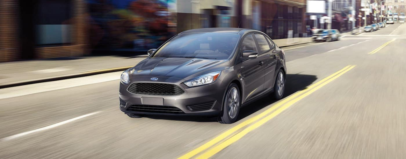 A silver 2016 Ford Focus is driving through a city.