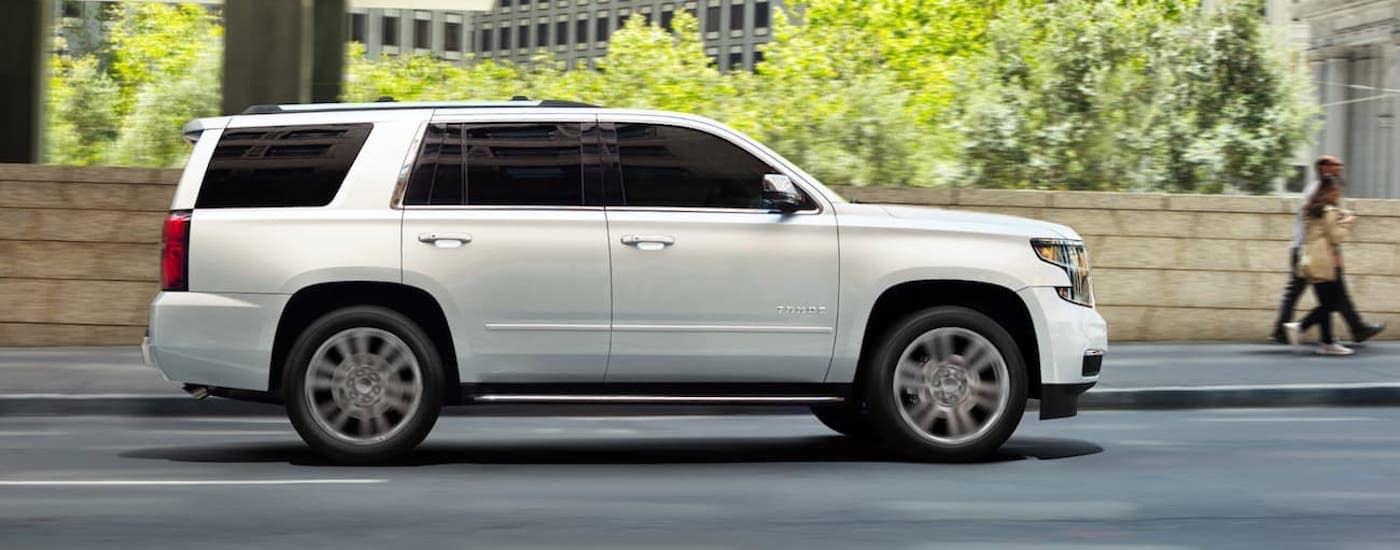 A white 2019 Chevy Tahoe is driving down an open road past a city after leaving a Louisville used car lot.
