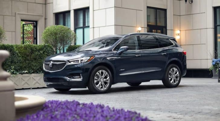 A black 2020 Buick Enclave Avenir is parked outside of a modern house.