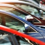 A close up shows used cars for sale parked at an angle.