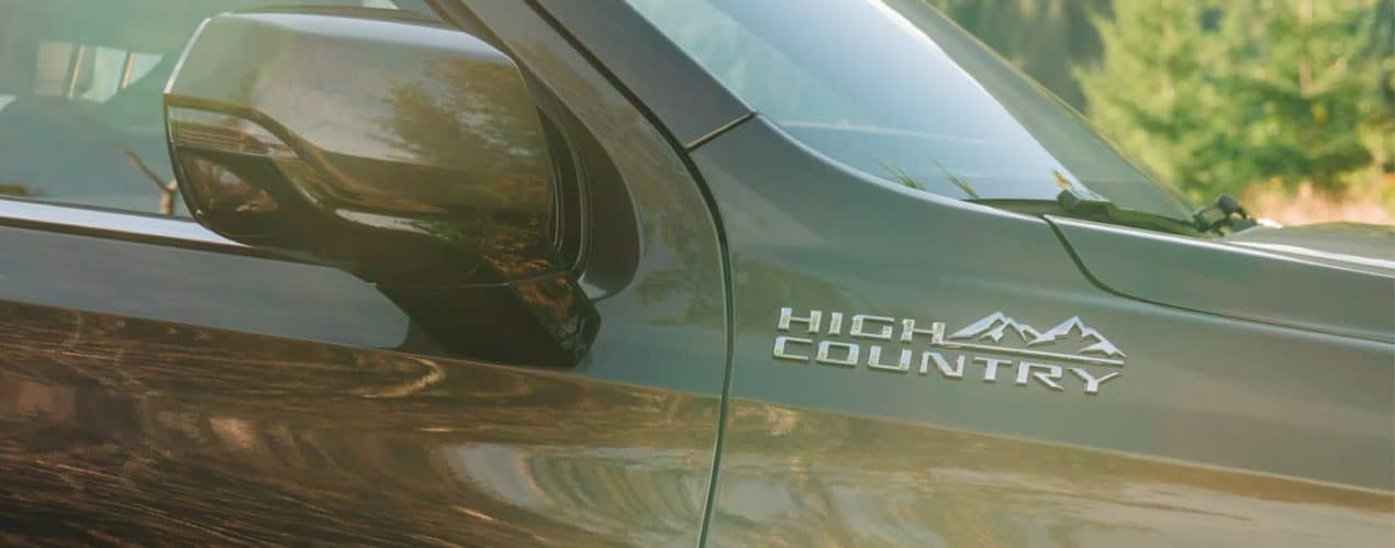 The 'High Country' badge is shown on the fender of a 2021 Chevy Tahoe High Country.