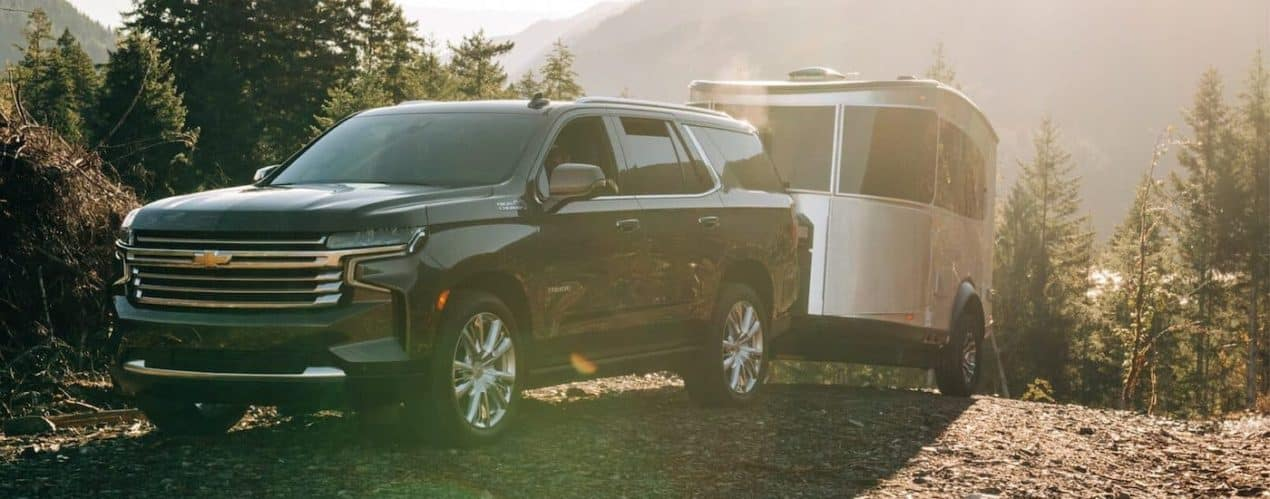 A black 2021 Chevy Tahoe High Country is shown towing a trailer on a sunny day.