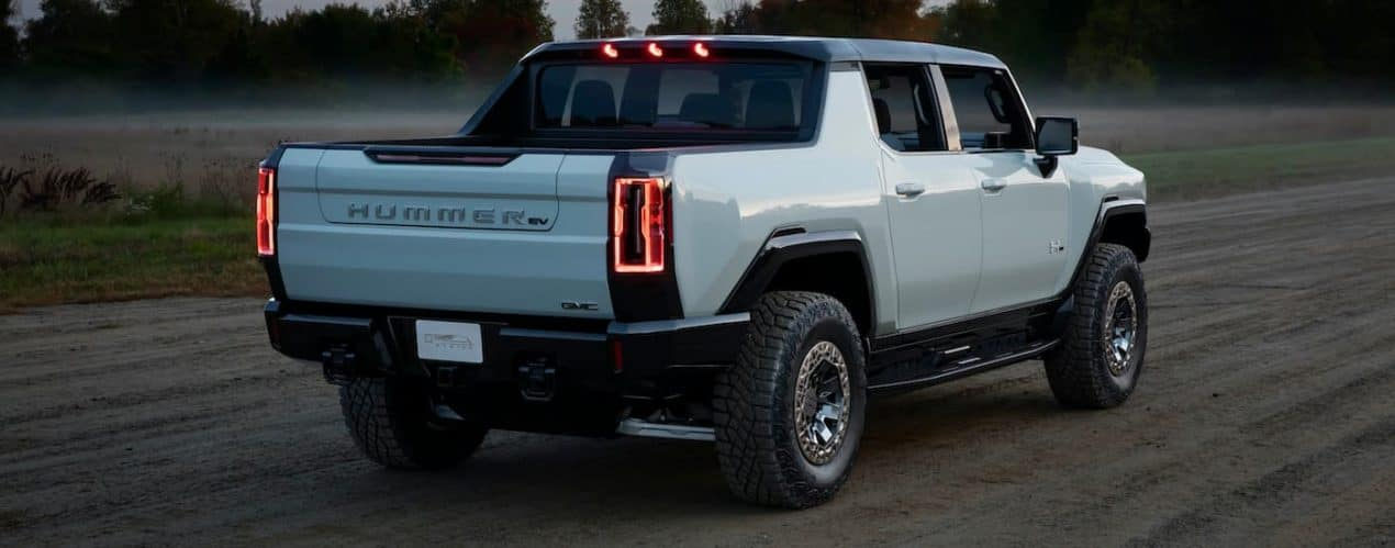 A white 2022 GMC Hummer EV Pickup is shown from the rear driving down a dirt path.