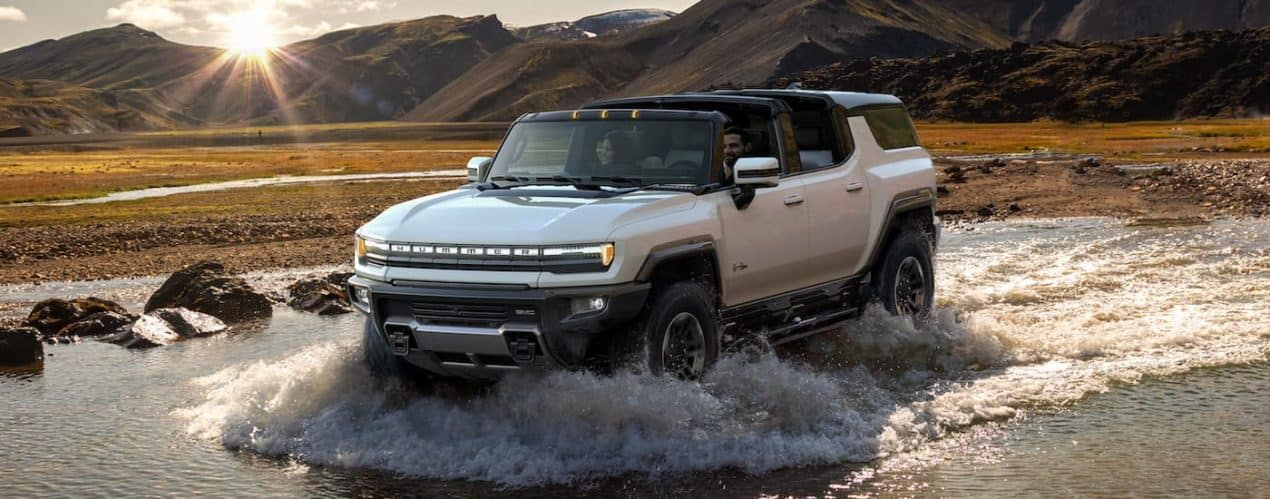 A white 2023 GMC Hummer EV SUV First Edition is shown driving through water with the sun shining.