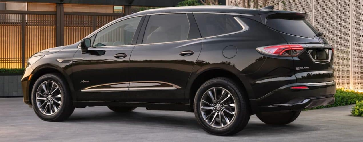 A black 2022 Buick Enclave is shown from the side parked in a modern driveway.