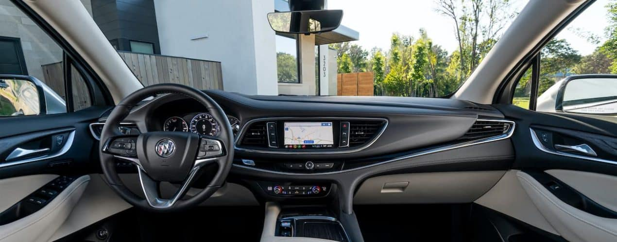 The black interior of a 2022 Buick Enclave shows the steering wheel and infotainment screen.