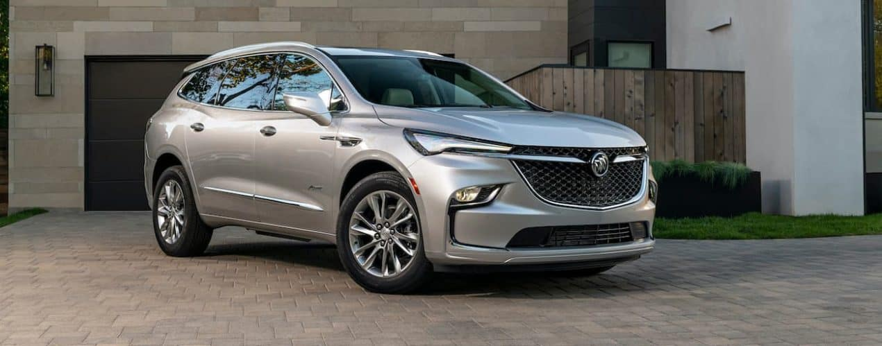 A silver 2022 Buick Enclave is shown parked in front of a modern house.