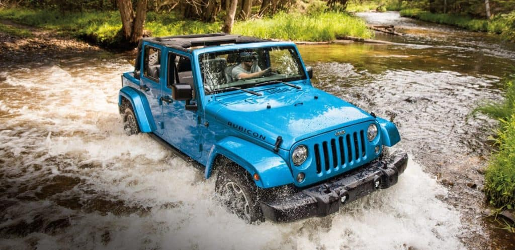 Blue 2018 jeep wrangler fording forested river