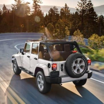 White Jeep Wrangler JK driving on forested road at sunset