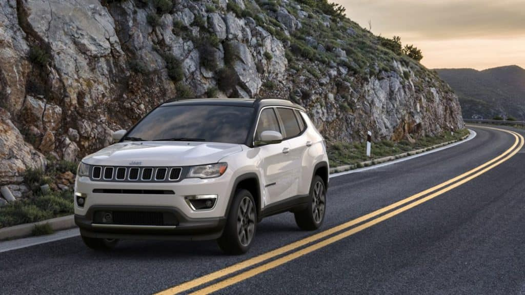 A white 2020 Jeep Compass driving along a mountain road in California