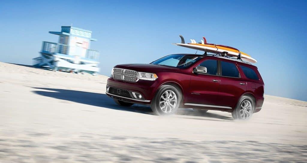 Maroon 2020 Dodge Durango driving down beach near Drive David
