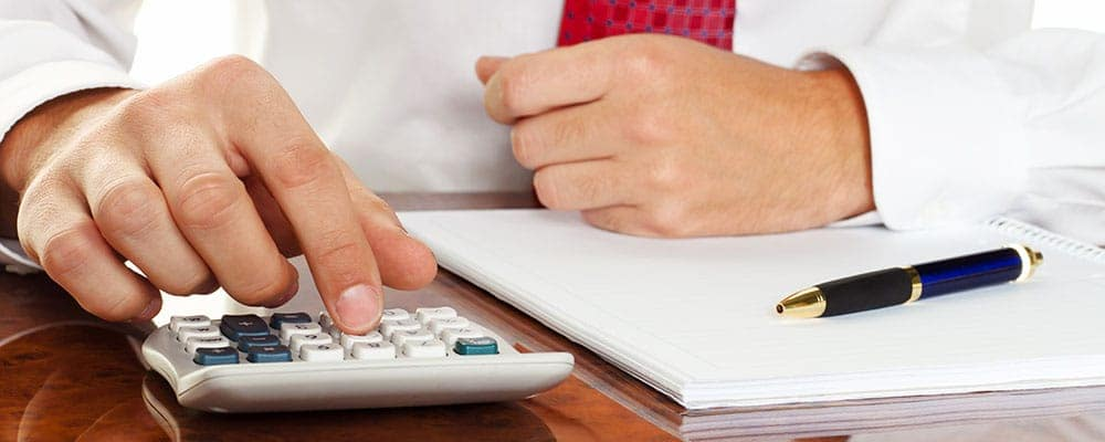Businessman with a calculator. calculation of costs, revenue, balance sheet