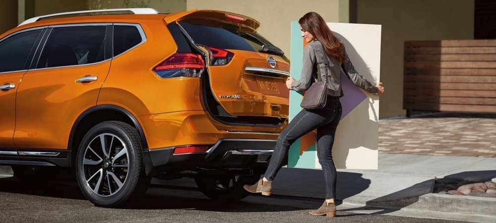 Woman Closing Truck of Orange Nissan Rogue