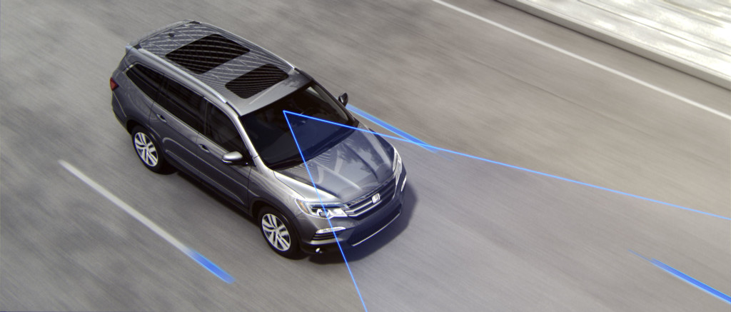 Silver Honda Odyssey driving on highway with blue cone in front of it representing lane departure warning