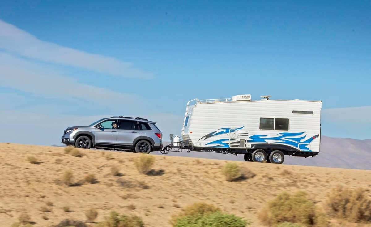 Silver 2019 Honda Passport towing white trailer in desert