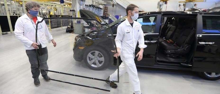 Two Honda R&D Americas, Inc. associates in Ohio prepare to install a sealed clear polycarbonate (plastic) barrier in a modified Honda Odyssey specially outfitted to transport people potentially infected with COVID-19 and healthcare workers.