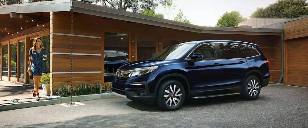 Woman walking up to her blue 2020 Honda Pilot parked in front of single-story home