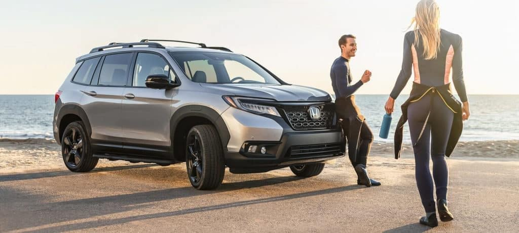 Woman in diving suit walking up to man in diving suit leaning on silver 2020 Honda Passport near beach