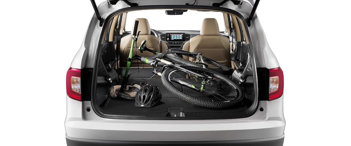 Open trunk of 2021 Honda Pilot with up to 109 cubic feet of cargo space and bike and other goods inside