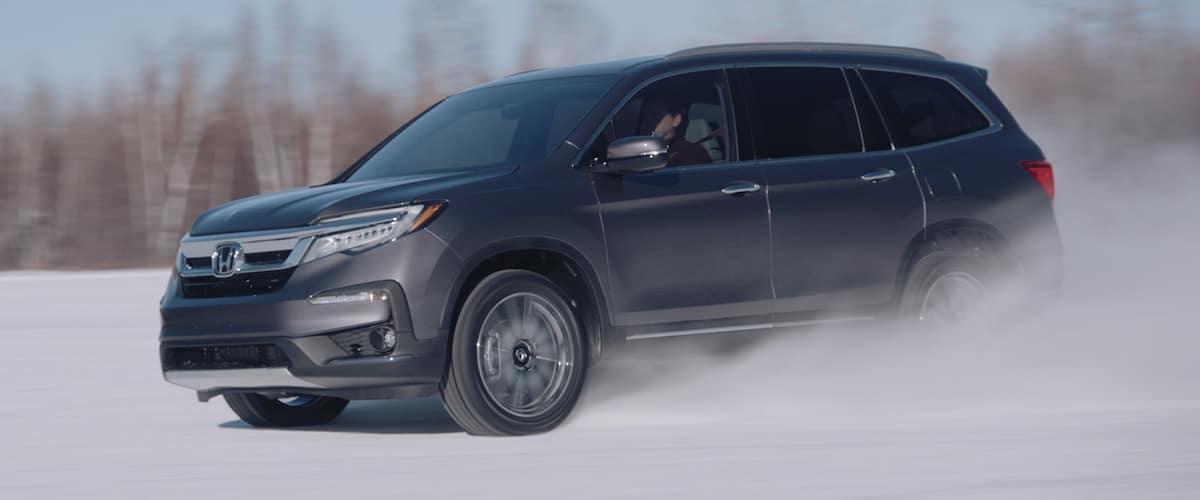 Black 2021 Honda Pilot with AWD driving through snow