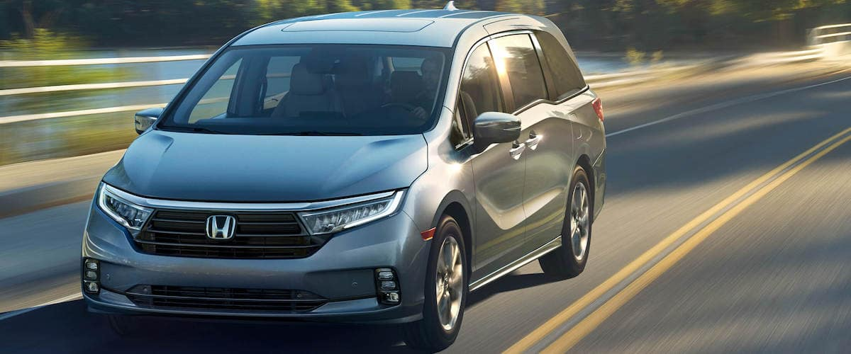 Silver 2021 Honda Odyssey driving on blurred road with sun reflecting off it
