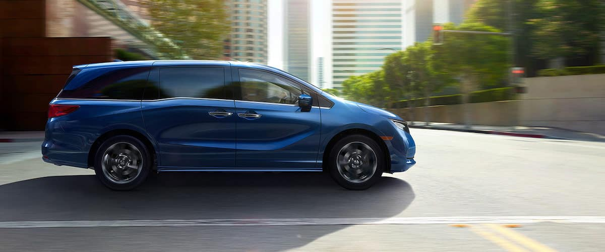 Side view of blue 2021 Honda Odyssey driving on city street