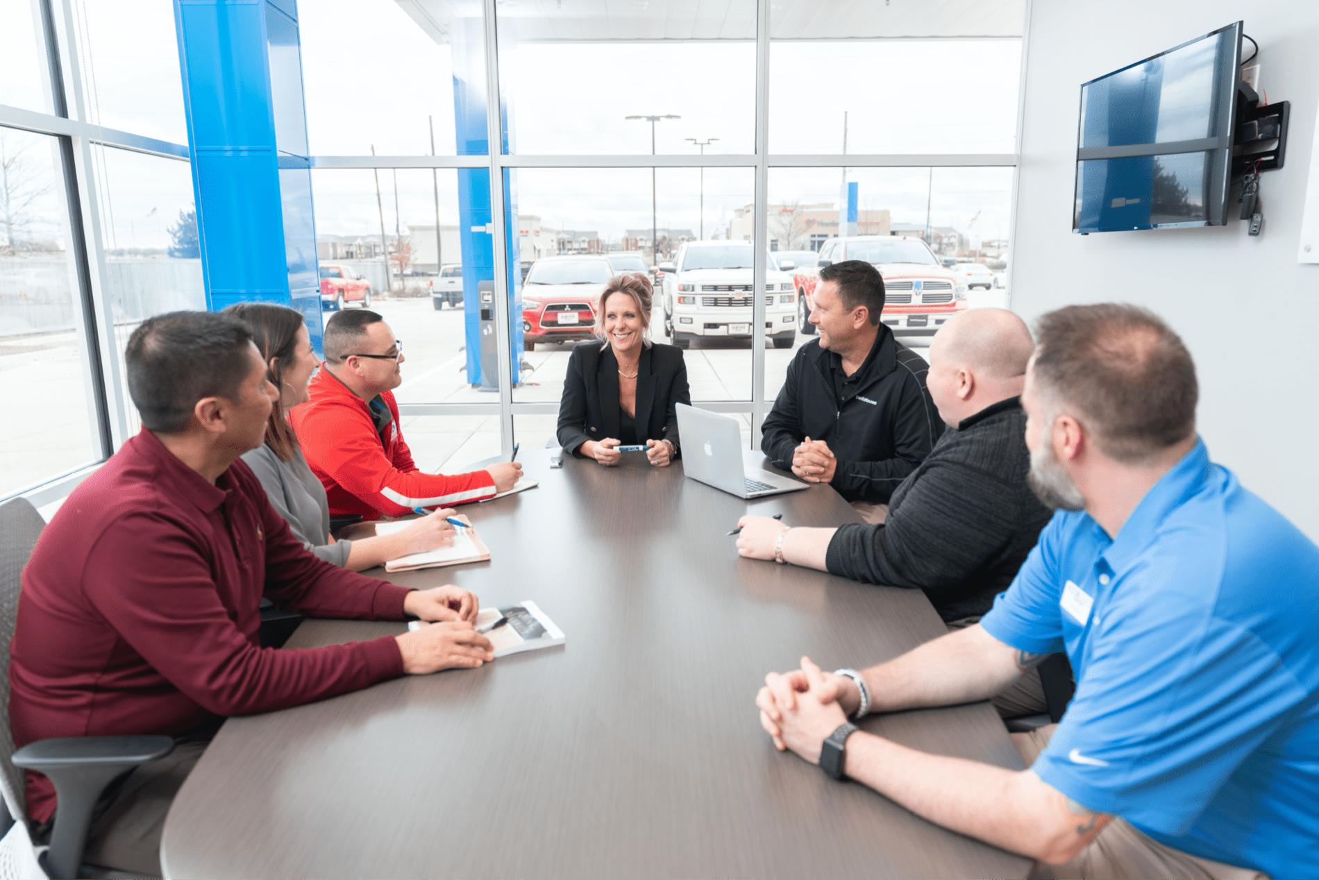 car salespersons meet in board room