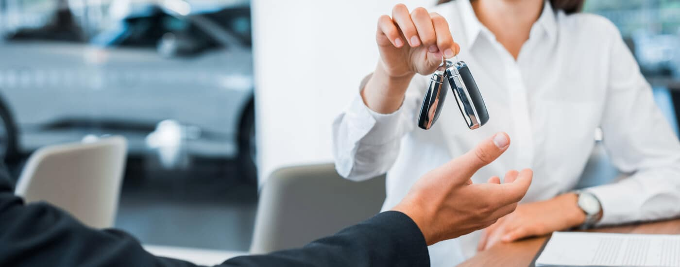 Cropped view of happy car dealer giving car key to man