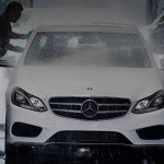 A white Mercedes-Benz going through a car wash with a man hand washing it.