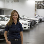 A service adviser standing by a long line of cars with her hand in her pocket