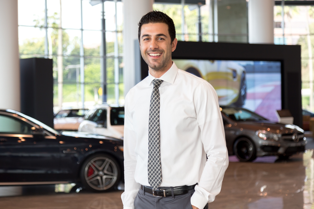 A tall man smiling and standing in the dealership with a white shirt and a checkered tie