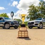 two mercedes-benz vehicles parked infront of golf trophy