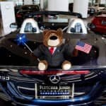 stuffed bear toy with suit on holding american flag on hood of car