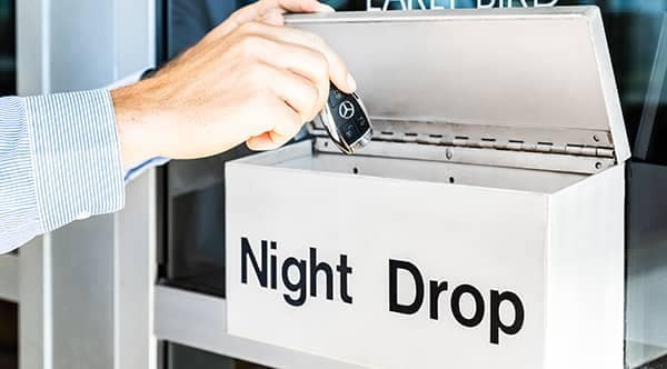 person putting car keys into a box labeled Night Drop