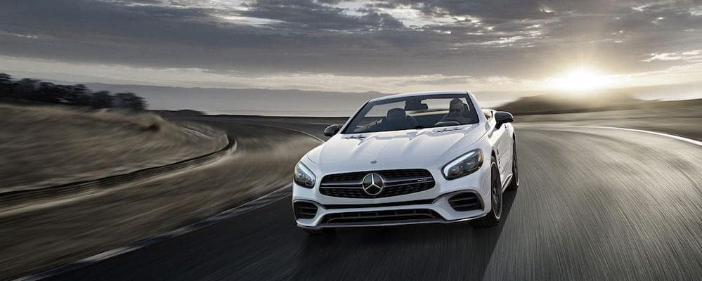 White Mercedes-AMG SL-Class Roadster speeding around curve on highway