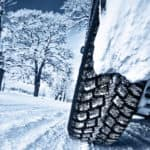Closeup of car tire while driving in snow