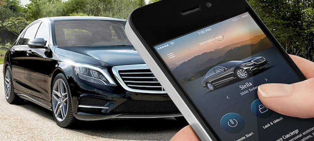 Hand holding iPhone with Mercedes me app pulled up facing parked Mercedes-Benz car