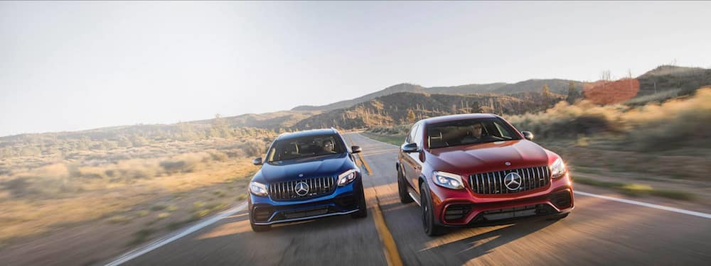 Two Mercedes-Benz SUVs racing side-by-side on a desert highway