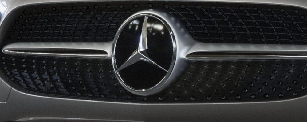 Mercedes-Benz logo on front grille of vehicle