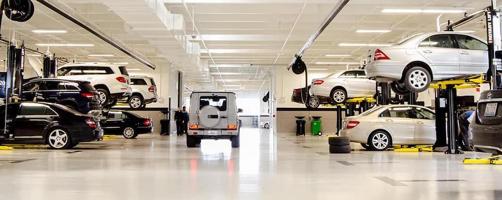 Mercedes-Benz service garage with vehicles on lifts and G Wagon exiting the garage