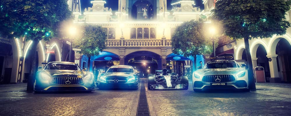 Mercedes-AMG racing vehicles parked in a row on cobblestone street at night with headlights on