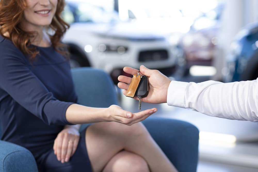 Close-up of seller giving keys of car to smiling woman after transaction in the salon
