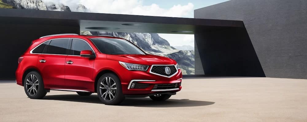 Red 2019 Acura MDX in profile in front of stylish mountain home