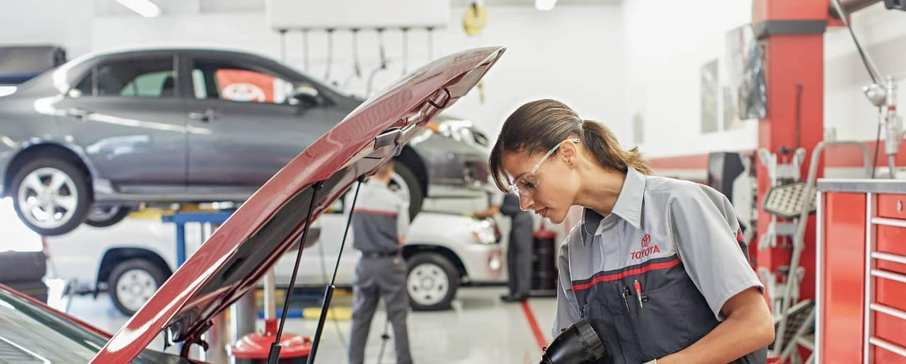 Woman Service Tech works on Toyota