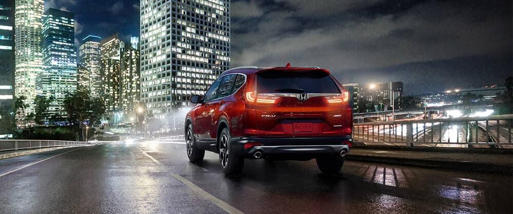 2018 Honda CR-V entering a light night rainswept cityscape