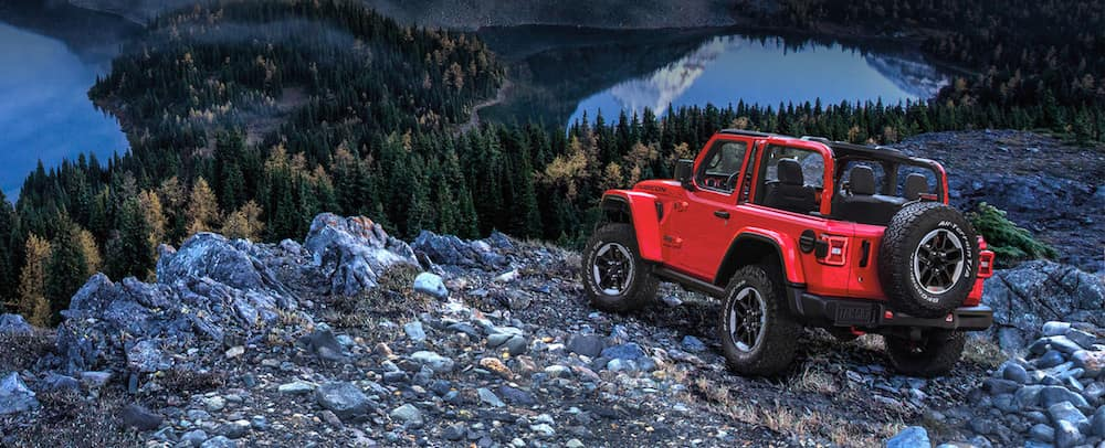 Red Jeep Wrangler with doors taken off parked atop a cliff