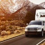 White Ram 1500 towing a trailer in front of a mountain