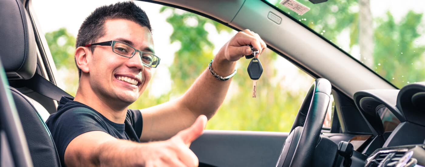 Man giving thumbs up holding keys in a car