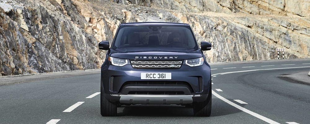 2019 Land Rover Discovery front view in dark gray driving on mountain highway
