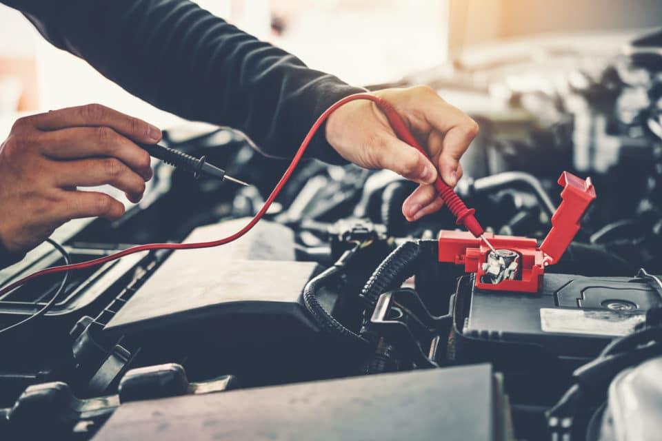 Technician Hands of car mechanic working on car battery